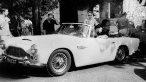 Peter Ustinov in zijn Aston Martin DB4 Series IV Vantage Convertible in 1962